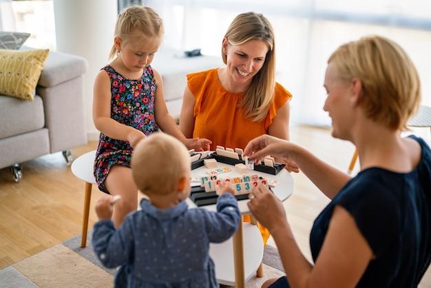 Famille à la table jouant à un jeu de société avec des enfants. couple de lesbiennes, crèche, concept d'enfance.