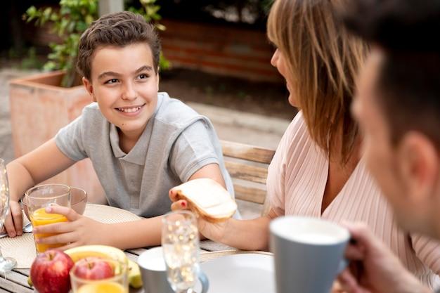 Famille en train de déjeuner ensemble à l'extérieur