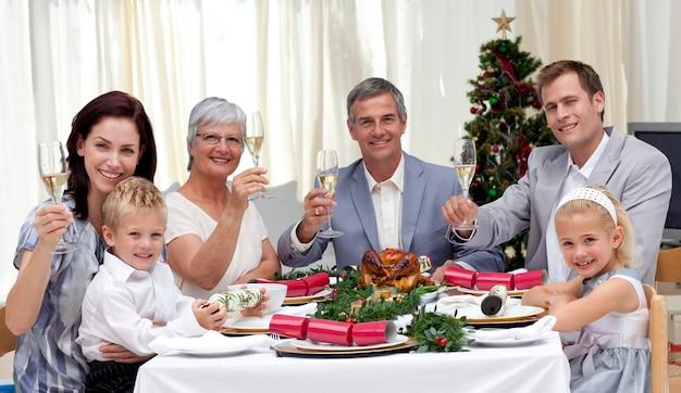 Famille en train de faire un repas de noël avec du vin blanc