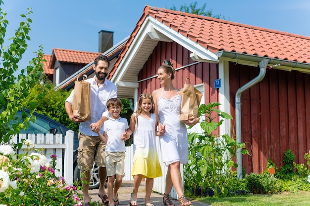 Famille transportant des produits d'épicerie de voiture à maison dans des sacs en papier