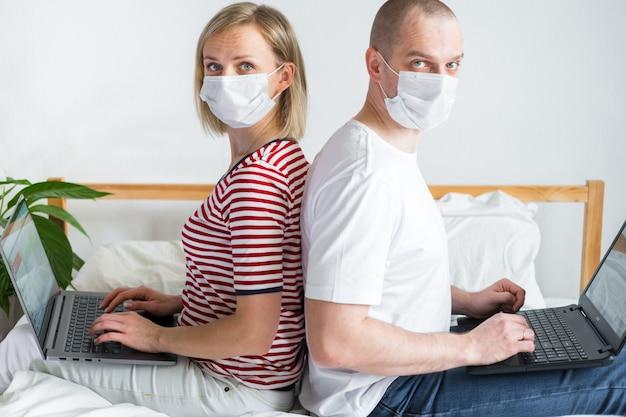 Famille travaillant à distance de l'emplacement de la maison dos à dos sur le lit. coronavirus en couple en quarantaine dans des masques médicaux. enseignement à distance, éducation et travail. commander des produits alimentaires en ligne
