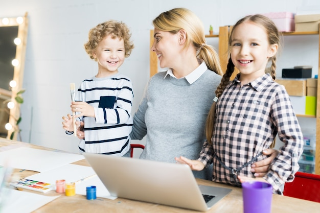 Famille de trois enfants apprenant à dessiner