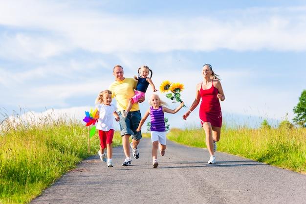 Famille avec trois enfants courir en bas d'une colline en été