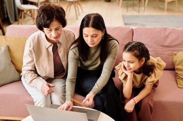 Famille de trois générations commandant des vêtements dans une boutique en ligne à loisir