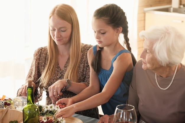 Famille de trois grand-mère mère et fille assise à la table et en train de dîner ensemble
