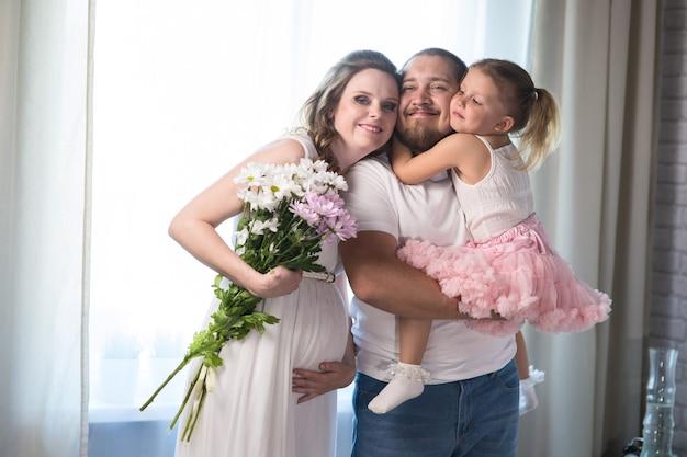 Une famille de trois. maman enceinte, papa et petite fille. embrassez la femme enceinte et caressez son ventre. heureux et en attente de la naissance d'un nouvel enfant