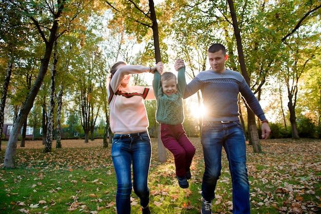 Famille de trois personnes profiter d'un parc en automne s'amuser sourire