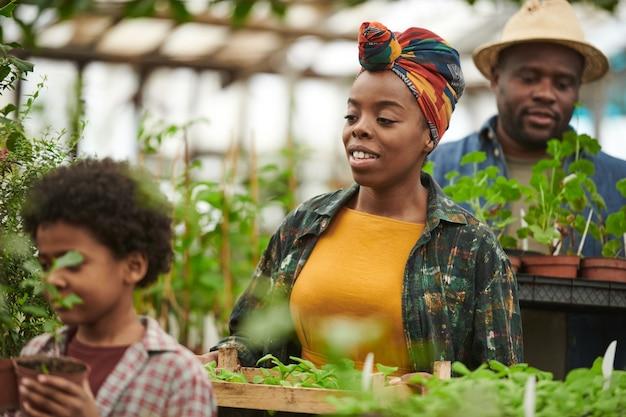 Famille de trois semis plantant ensemble tout en travaillant dans le jardin
