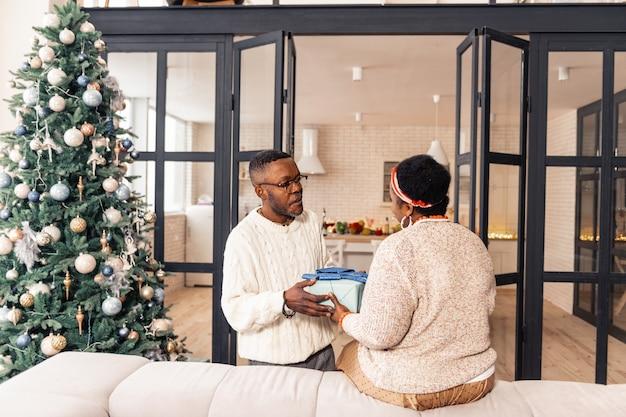 Famille unie. belle femme positive regardant son frère tout en lui prenant un cadeau