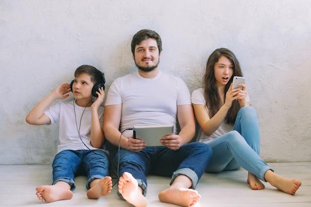Famille utilisant différents appareils et posant