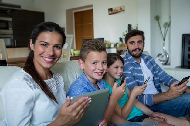 Famille utilisant un ordinateur portable et un téléphone portable dans le salon à la maison