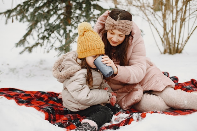 Famille en vacances dans la forêt enneigée