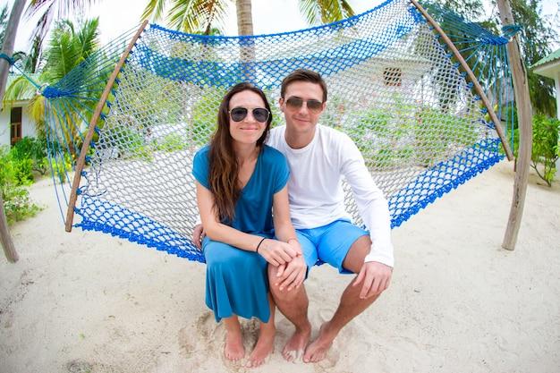 Famille en vacances d'été se détendre dans un hamac