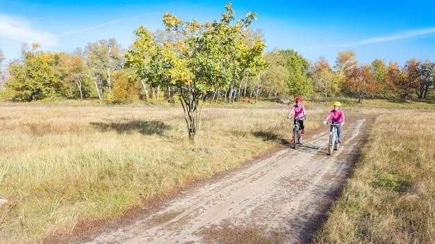 Famille à vélo automne vélo à l'extérieur, mère active et enfant à vélo, vue aérienne de famille heureuse avec enfant dans le parc d'automne par le haut, sport et concept de remise en forme