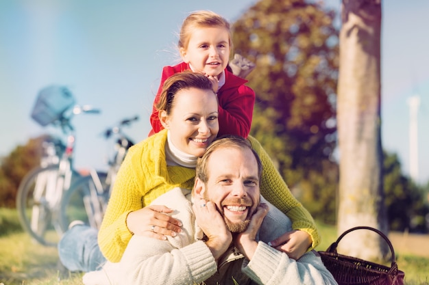 Famille à vélo dans un parc en automne