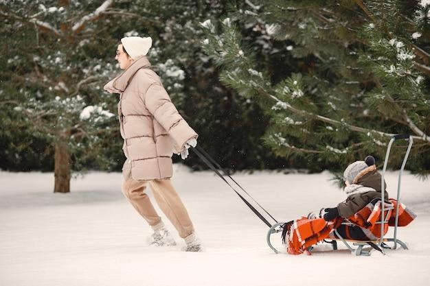 Famille en vêtements d'hiver en vacances dans la forêt enneigée