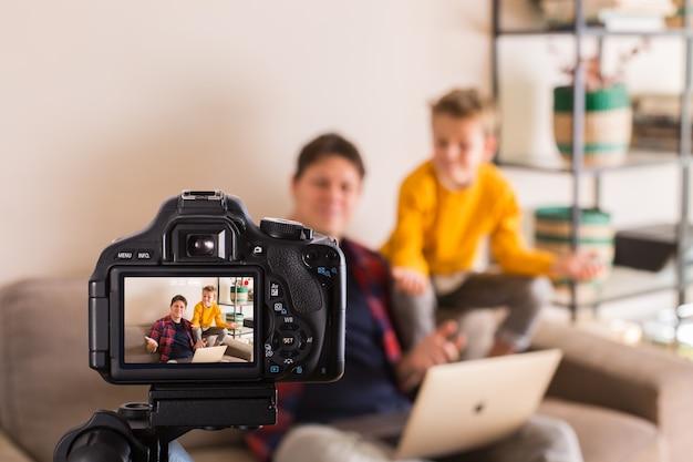 Famille de vlogger enregistrant une vidéo sur les réseaux sociaux assis sur un canapé