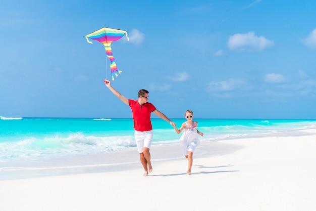 Famille voler cerf-volant ensemble à la plage blanche tropicale