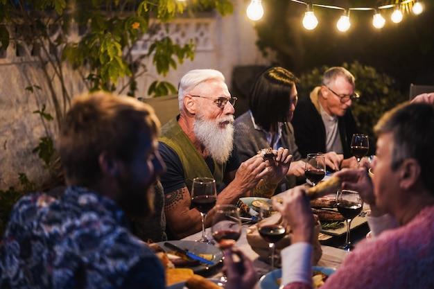 Familles mangeant au dîner barbecue - amis multiraciaux savourant un repas en plein air - concept de nourriture, d'amitié, de rassemblement et de mode de vie estival - focus sur le visage de l'homme hipster
