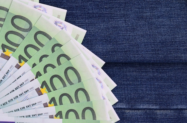 Le fan de beaucoup de billets en euros est sur une surface de denim sombre