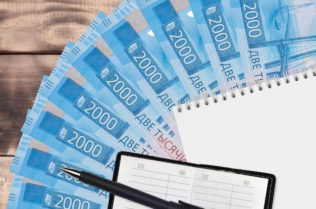 Fan de billets de 2000 roubles russes et bloc-notes avec carnet de contacts et stylo noir. concept de planification financière et stratégie d'entreprise