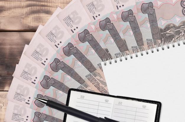 Fan de billets de roubles russes et bloc-notes avec carnet de contacts et stylo noir