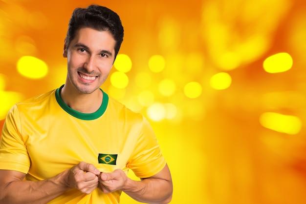 Fan brésilien célèbre sur fond jaune