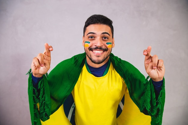 Fan brésilien avec un drapeau sur le dos acclamant avec les doigts croisés pour que le brésil gagne