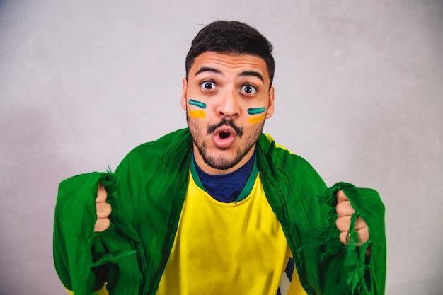 Fan brésilien avec un drapeau sur le dos encourageant le brésil à gagner