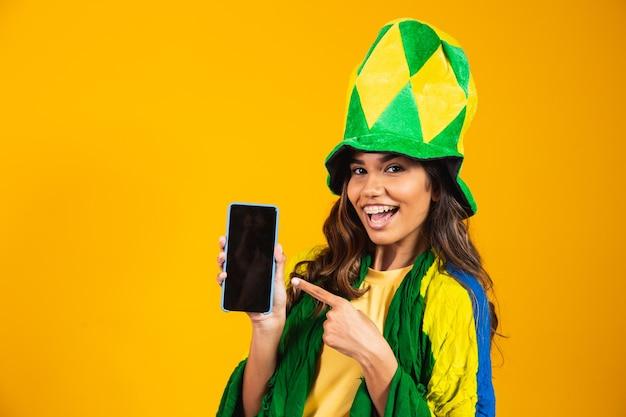 Fan brésilien. portrait, fan brésilienne montrant son téléphone portable, habillée en fan de football ou en match de football sur fond jaune. couleurs du brésil.coupe du monde