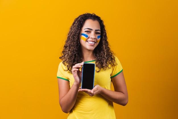 Fan brésilien tenant un smartphone avec espace de copie
