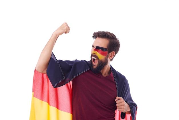 Fan extatique avec le drapeau de l'allemagne acclamant