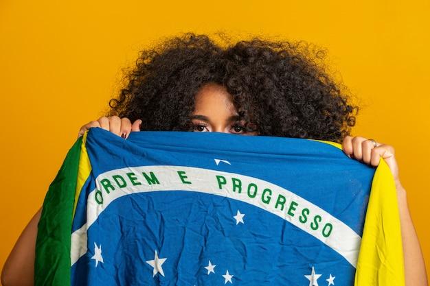 Fan de femme mystérieuse noire tenant un drapeau brésilien sur votre visage. couleurs du brésil en mur, vert, bleu et jaune. élections, football ou politique.