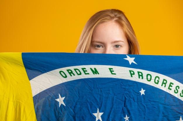 Fan de femme rousse mystérieuse tenant un drapeau brésilien sur votre visage. le brésil colore le drapeau, vert, bleu et jaune. élections, football ou politique.