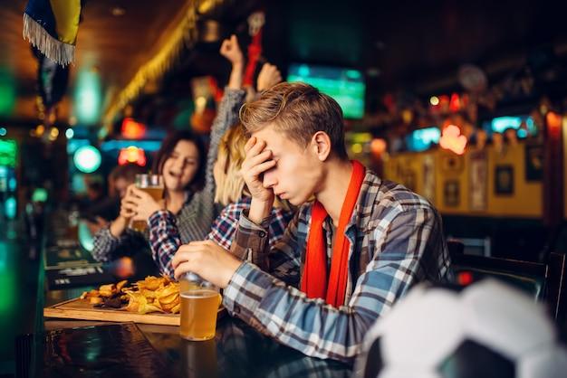Fan de football bouleversé assis au comptoir du bar des sports. diffusion télé, défaite de l'équipe favorite, game over
