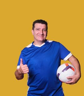 Fan de football masculin donne les pouces vers le haut sur un mur isolé