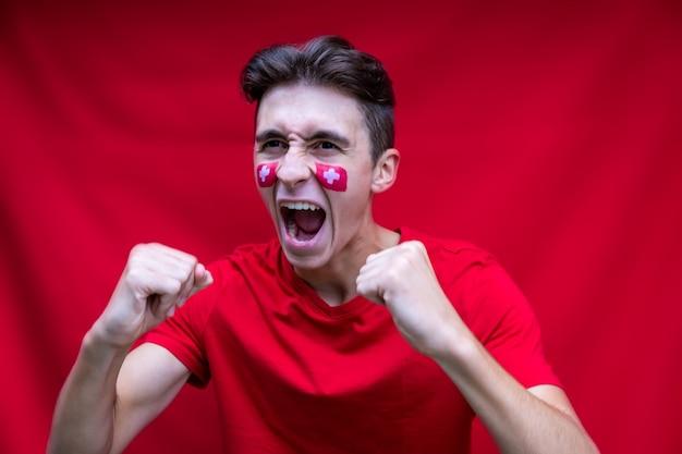 Fan de football suisse criant pour son équipe nationale isolée sur fond rouge drapeau peint