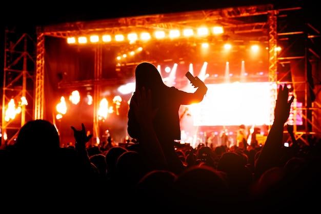 Fan de musique appréciant les performances nocturnes d'un artiste célèbre sur scène et en utilisant son smartphone