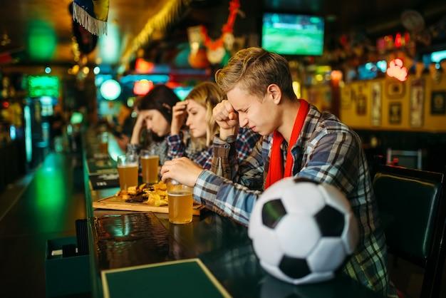 Fan triste couvre le visage avec les mains dans le bar des sports