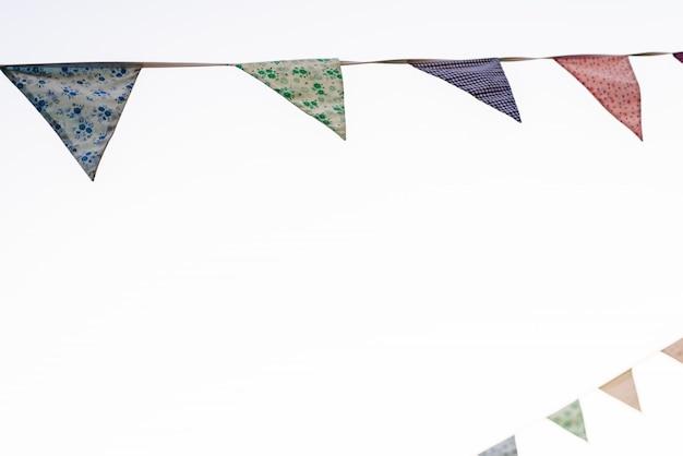 Fanions avec fond de ciel bleu et couleurs pâles suspendus à une corde traversant l'image lors d'un événement en plein air, espace pour le texte.
