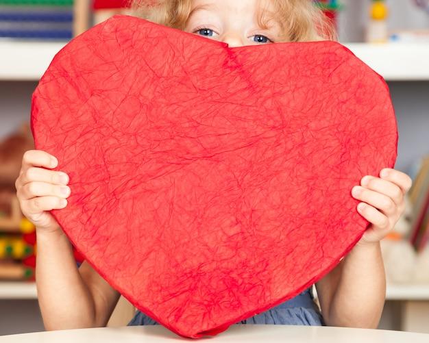 Fanny baby avec grand coeur de papier rouge concept de saint valentin