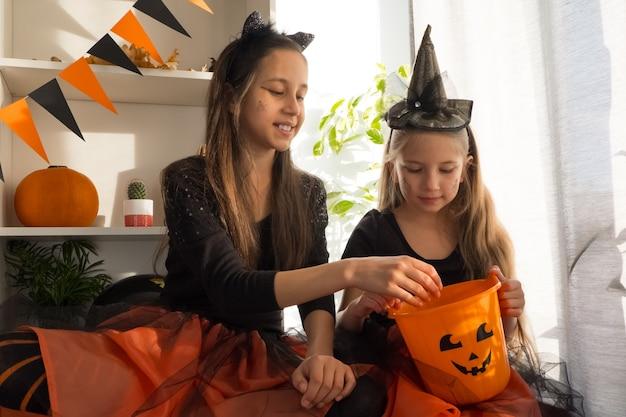 Fanny filles sœurs de dix et sept ans en costumes de sorcière à halloween célèbrent les vacances ...