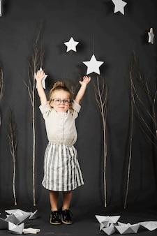 Fanny petite fille avec des lunettes sur fond gris avec des étoiles, des arbres et des bateaux en papier