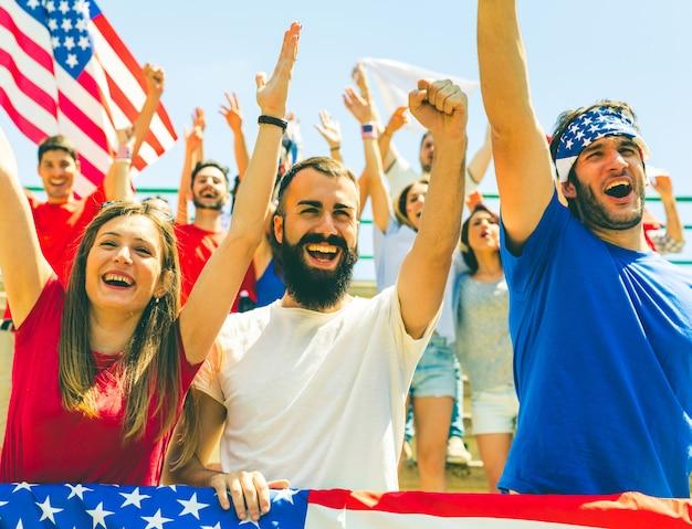 Fans américains acclamant au stade avec les drapeaux des états-unis