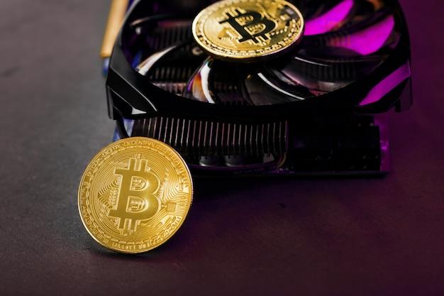 Sur les fans d'une carte vidéo puissante, les pièces de la crypto-monnaie bitcoin avec un rétro-éclairage rouge sont affichées. le concept de minage et d'extraction de crypto-monnaie une ferme de crypto-monnaie.