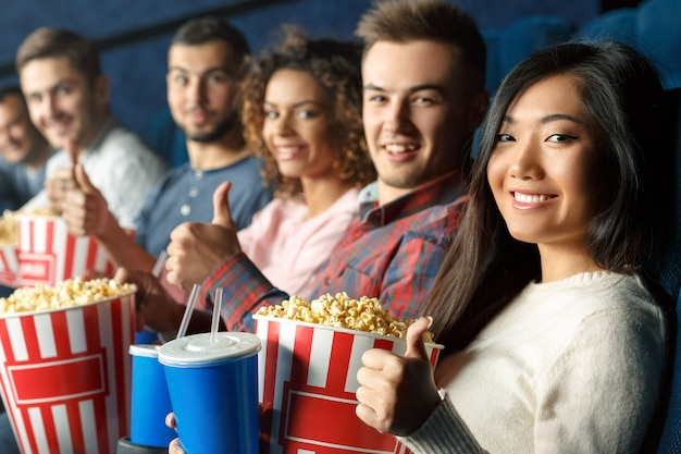 Les fans de cinéma tous ici. groupe d'amis gais montrant les pouces vers le haut ensemble assis dans la salle de cinéma