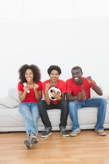 Fans de football assis sur un canapé, acclamant ensemble à la maison dans le salon