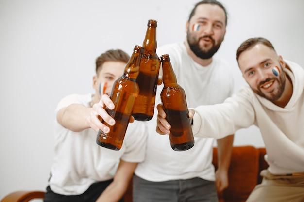 Fans de football assis sur le canapé dans le salon et boire de la bière