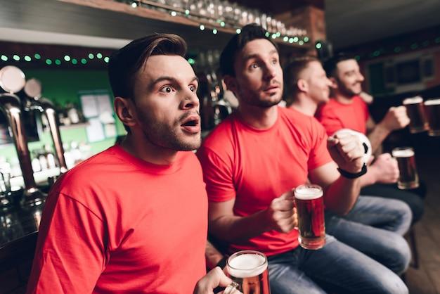 Les fans de football attendent le but au bar des sports