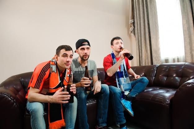 Fans de football. les hommes boivent de la bière, mangent des frites et des racines pour le football.